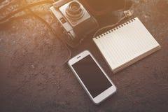 有照相机的巧妙的在ructic桌上的电话和笔记本 图库摄影