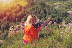 有照相机的微笑的妇女在山顶部 免版税库存图片