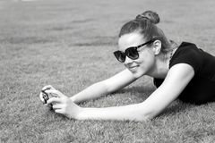 有照相机的愉快的女孩在绿草在巴黎,法国 库存照片