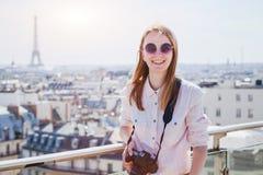 有照相机的愉快的微笑的妇女游人在巴黎,观光或者旅行背景中 免版税库存照片