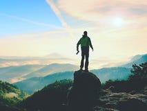 有照相机的摄影师在山顶部的手上 远足者在岩石峰顶上升了在有雾的谷上的 库存图片