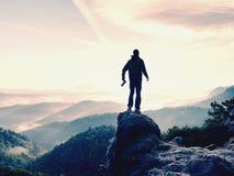 有照相机的摄影师在山顶部的手上 远足者在岩石峰顶上升了在有雾的谷上的 免版税库存照片
