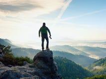 有照相机的摄影师在山顶部的手上 远足者在岩石峰顶上升了在有雾的谷上的 免版税库存图片