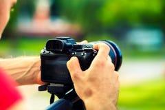 有照相机的旅行摄影师在自然背景在手中做照片 免版税库存图片