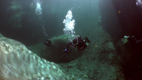 有照相机的潜水者水下在透明河Verzasca 股票录像