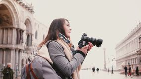 有照相机的美丽的白种人自由职业者的新闻工作者为古老大厦照相的在圣马尔谷教堂广场,威尼斯 股票录像
