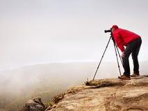 有照相机的远足者在三脚架拍从岩石山顶的照片 山顶的单独摄影师 免版税库存图片