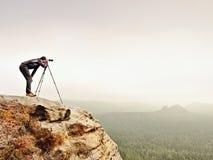 有照相机的远足者在三脚架拍从岩石山顶的照片 山顶的单独摄影师 免版税库存照片