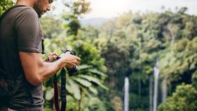 有照相机的年轻人由瀑布在森林里 库存照片