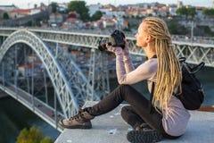 有照相机的年轻旅游妇女坐在Dom我横跨杜罗河河跨接在波尔图的雷斯对面的观察平台 图库摄影
