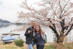 有照相机的更老的人在他的脖子举行年轻亚洲夫人wi 免版税图库摄影