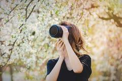 有照相机逗留的少女在开花的树附近 库存照片