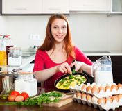 有煮熟的omlet的妇女在平底锅在家厨房里 图库摄影