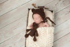有熊帽子和被充塞的熊玩具的新出生的男婴 免版税库存图片