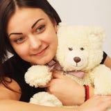 有熊玩具的美丽的妇女作为关心的标志乡情 库存照片