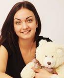 有熊玩具的美丽的妇女作为愉快的童年的标志 库存照片