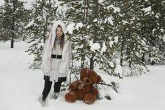 有熊的女孩在冬天森林里 图库摄影
