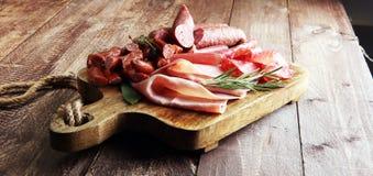 有熏火腿、烟肉、蒜味咸腊肠和香肠的大理石切板 免版税库存图片