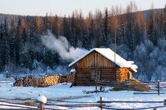 有熔炉和木柴的冬天房子 免版税库存照片