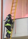 有爬一架木梯子的氧气瓶的消防队员 免版税库存照片