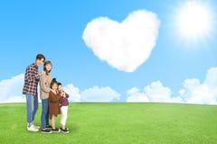 有爱云彩的幸福家庭在天空的 库存照片