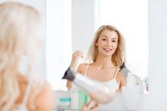 有爱好者干毛发的愉快的少妇在卫生间 图库摄影