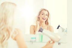 有爱好者干毛发的愉快的少妇在卫生间 免版税库存照片