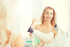 有爱好者干毛发的愉快的少妇在卫生间 免版税库存图片