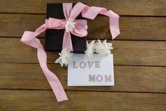 有爱妈妈文本的礼物盒在木板条 免版税库存图片