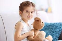 有爱拥抱玩具的滑稽的小女孩坐沙发 免版税库存照片