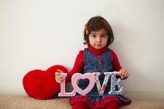 有爱标志和红色长毛绒心脏的女孩 免版税库存图片
