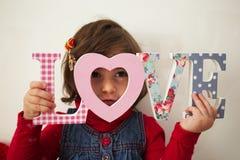 有爱标志和红色长毛绒心脏的女孩 免版税库存照片