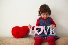 有爱标志和红色长毛绒心脏的女孩 库存照片