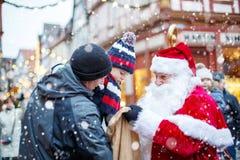 有父亲和圣诞老人的小小孩男孩在圣诞节市场上 免版税库存图片