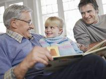 有父亲和祖父读书故事书的女孩 图库摄影