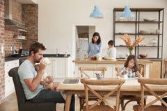有父亲工作的繁忙的房子作为母亲准备膳食 库存照片