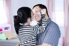 有父亲的小女孩在卧室 免版税库存图片