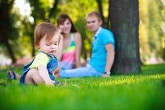 有父项的婴孩在一个美丽的夏天公园 库存照片