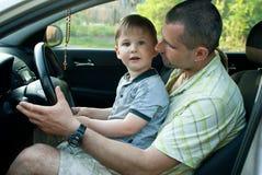 有爸爸的男孩学会驾驶汽车 免版税图库摄影