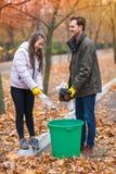 有爸爸的青少年的女孩干净在公园,把各种各样的袋子和塑料瓶扔出去在缸 外面 库存照片