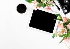 有片剂、办公室辅助部件、咖啡和花的办公桌 免版税库存照片