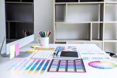 有片剂、图表设计师和颜色的现代办公室工作场所 图库摄影