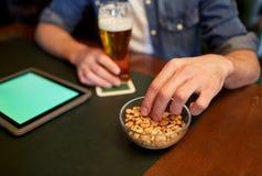 有片剂个人计算机、啤酒和花生的人在酒吧或客栈 图库摄影