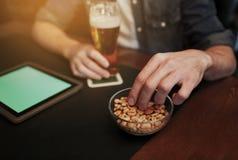 有片剂个人计算机、啤酒和花生的人在酒吧或客栈 免版税图库摄影