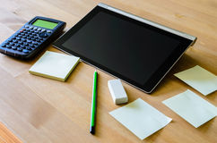 有片剂个人计算机、计算器、铅笔和稠粘的笔记的工作场所 免版税图库摄影