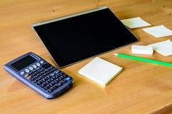 有片剂个人计算机、计算器、铅笔和稠粘的笔记的工作场所 免版税库存照片