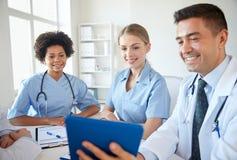 有片剂个人计算机会议的愉快的医生在医院 免版税库存照片