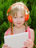 有片剂个人计算机听的音乐的逗人喜爱的女孩在headph 免版税库存图片