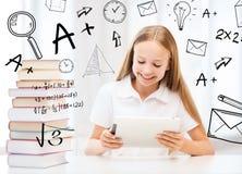 有片剂个人计算机和书的女孩在学校 免版税库存照片