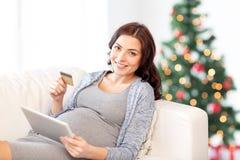 有片剂个人计算机和信用卡的孕妇 免版税库存图片